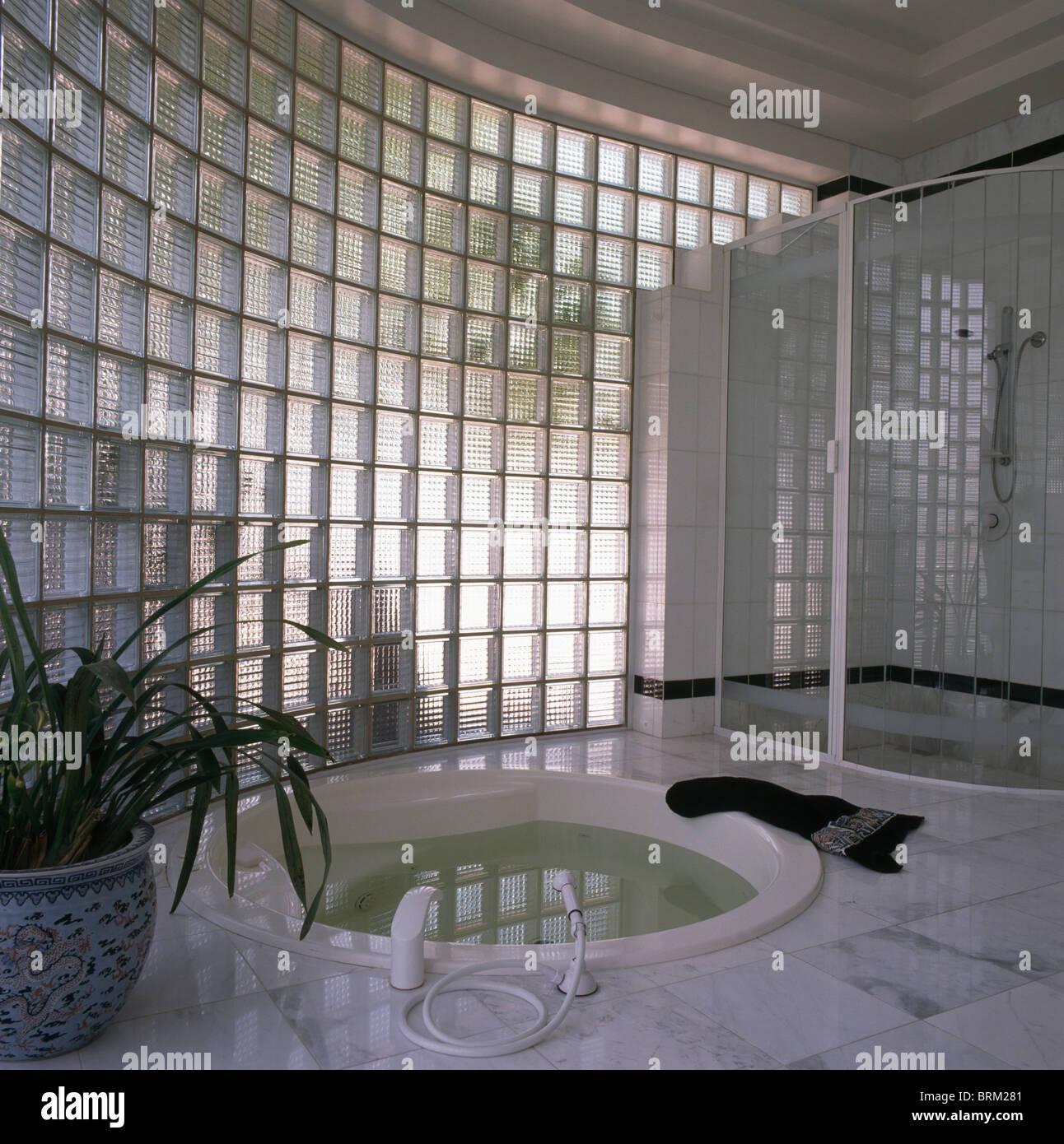 Gebogenes Glaswand im modernen Badezimmer mit versunkenen Whirlpool ...