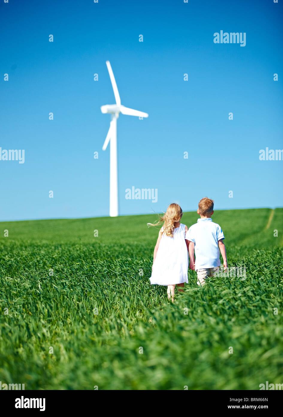 Jungen und Mädchen Lookng an Windturbine Stockbild