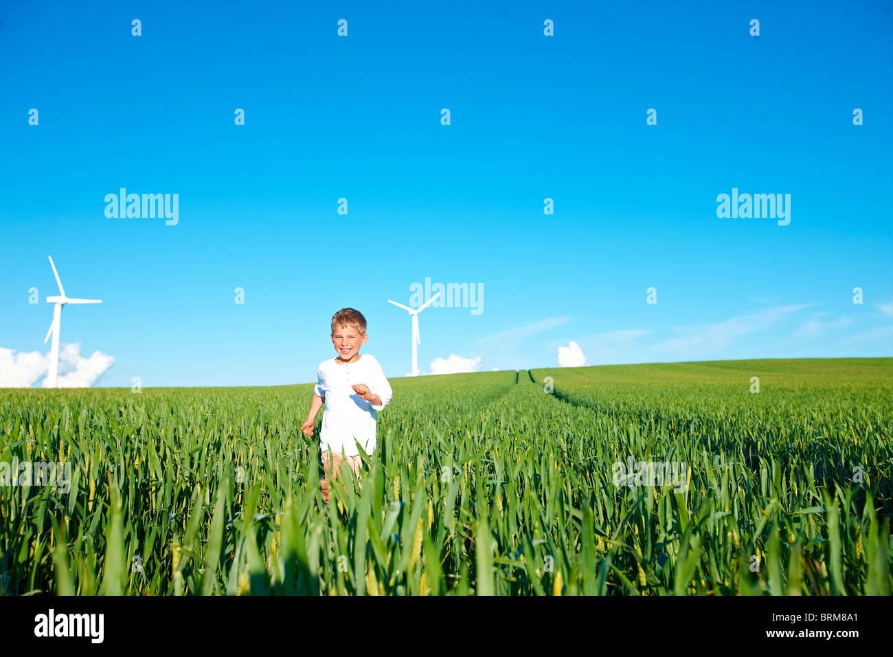 Junge läuft auf Feld mit Windrädern Stockbild