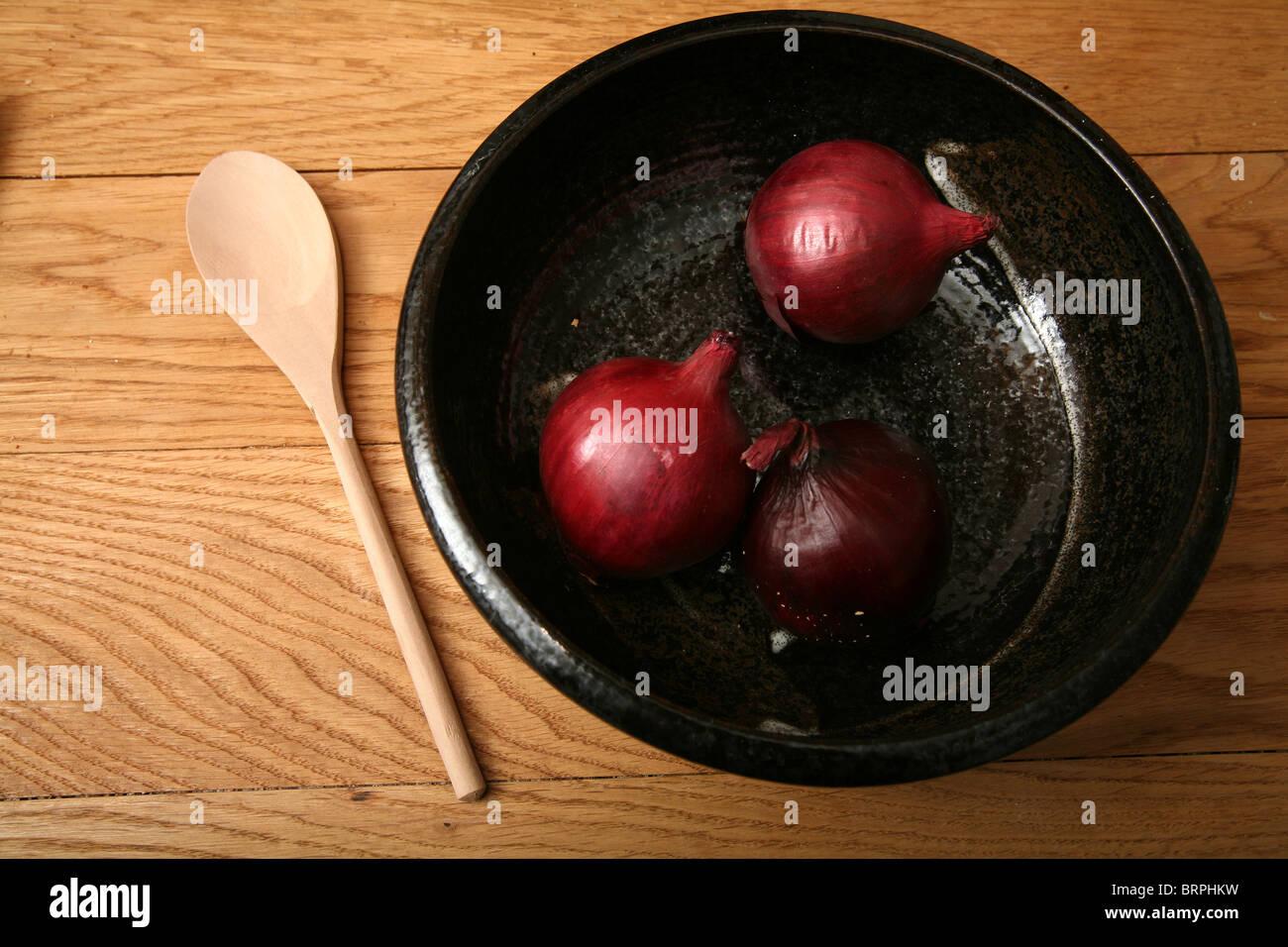 drei rote Zwiebeln in schwarz Schüssel auf einfachen hölzernen Hintergrund mit Holzlöffel Stockbild