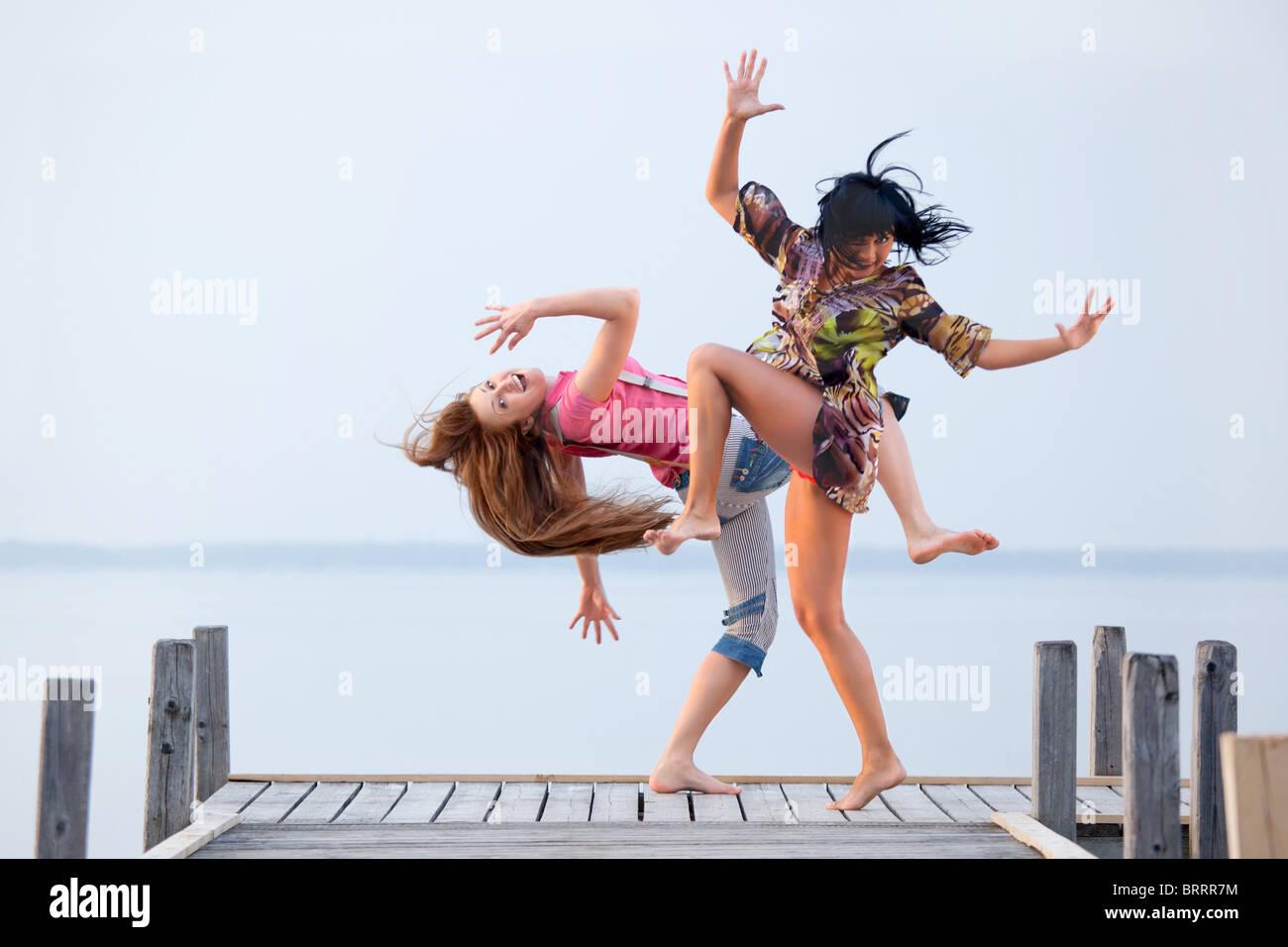 zwei Mädchen tanzen auf Grund von Wasser und Himmel Stockbild
