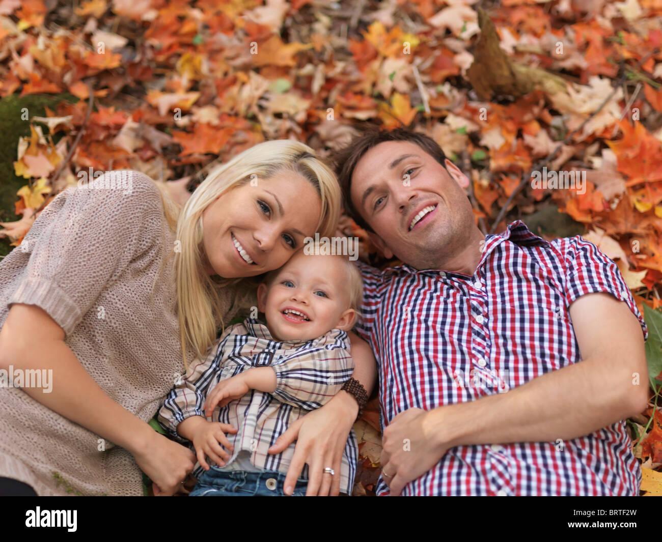 Glücklich lächelnde junge Eltern und ein zwei Jahre altes Mädchen auf bunten umgestürzten Baum Stockbild