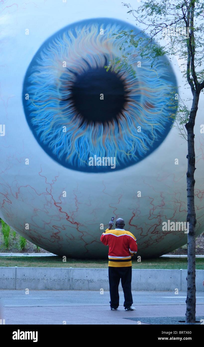 Tony Tassets 'Auge' Kunstwerk mit Mann stand vor ihr ein Foto auf seinem Handy unter Stockbild