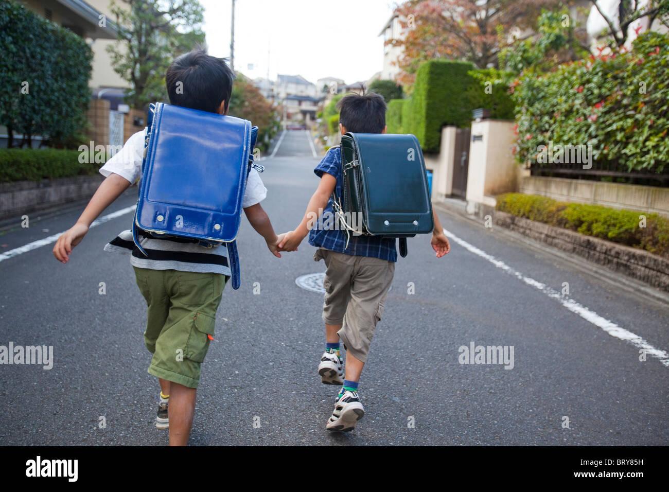 Jungen halten sich an den Händen und laufen, Präfektur Tokio, Honshu, Japan Stockfoto