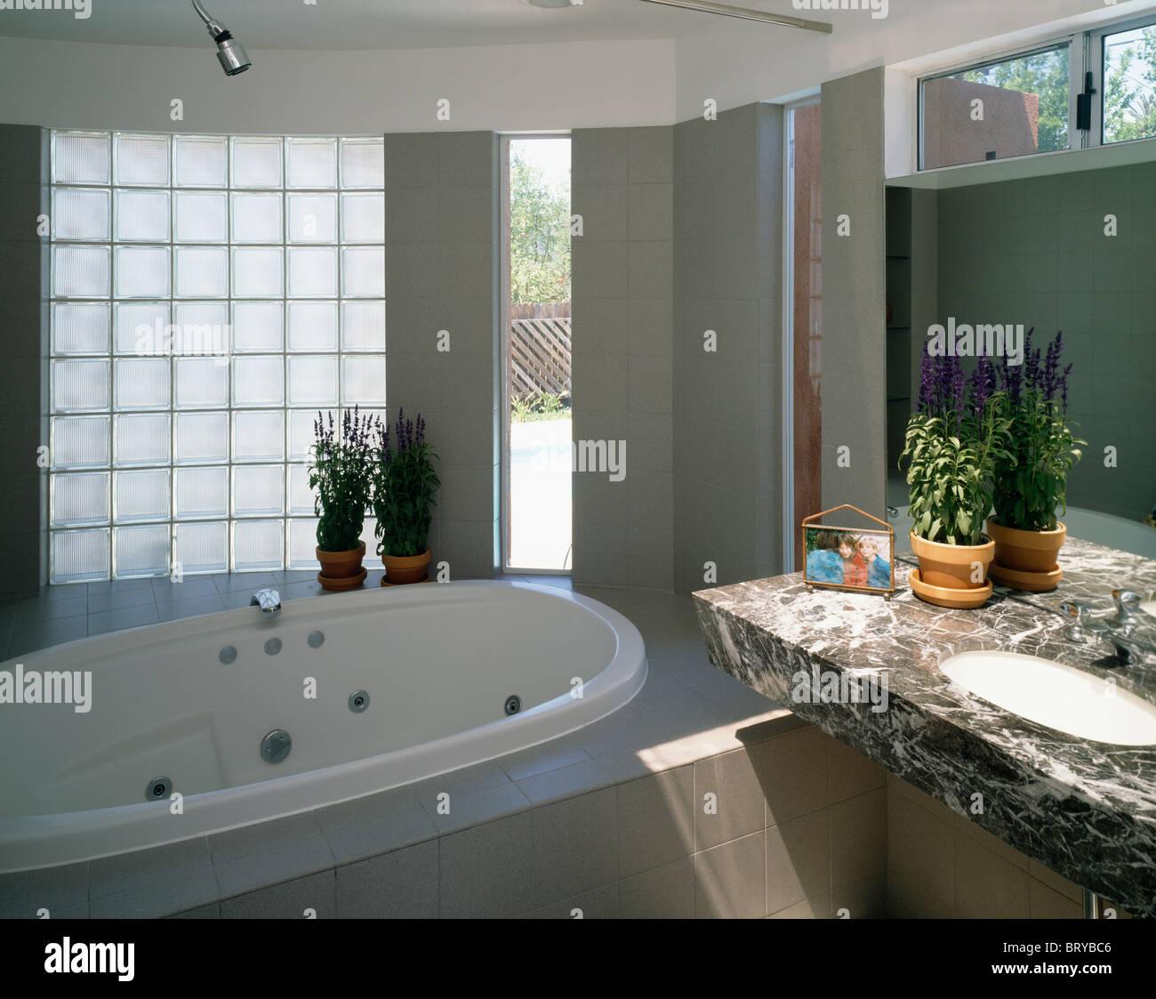 Ovale Whirlpool unter Glasbaustein Wand im modernen Badezimmer mit ...