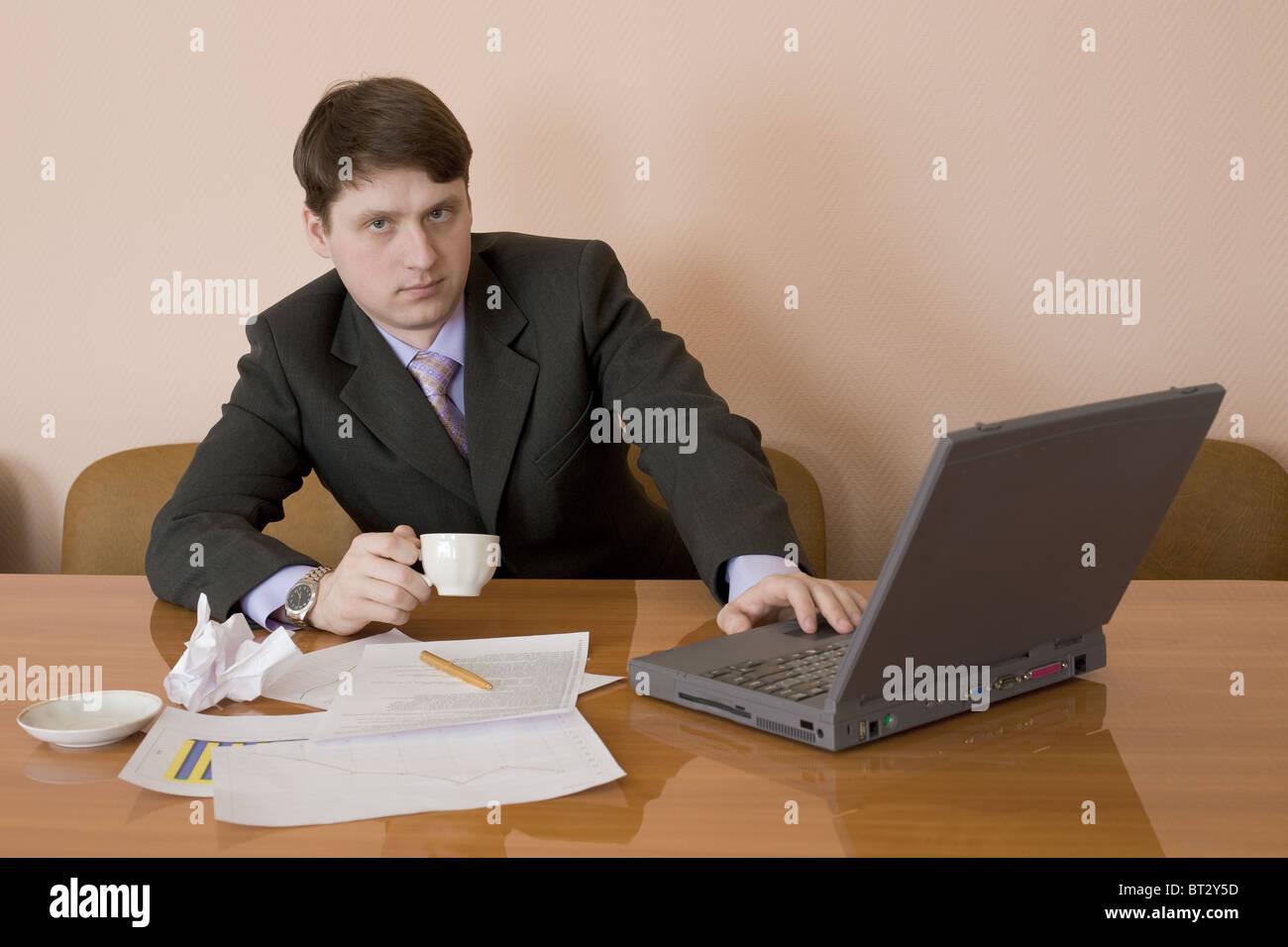Geschäftsmann auf einen Arbeitsplatz mit Laptop und eine Kaffeetasse Stockfoto