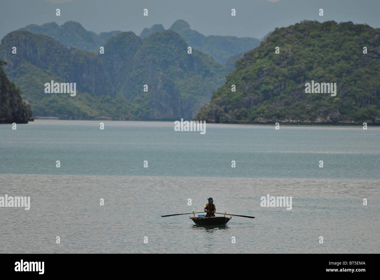 Mann-Ruderboot in Halong Bucht, Vietnam Stockfoto