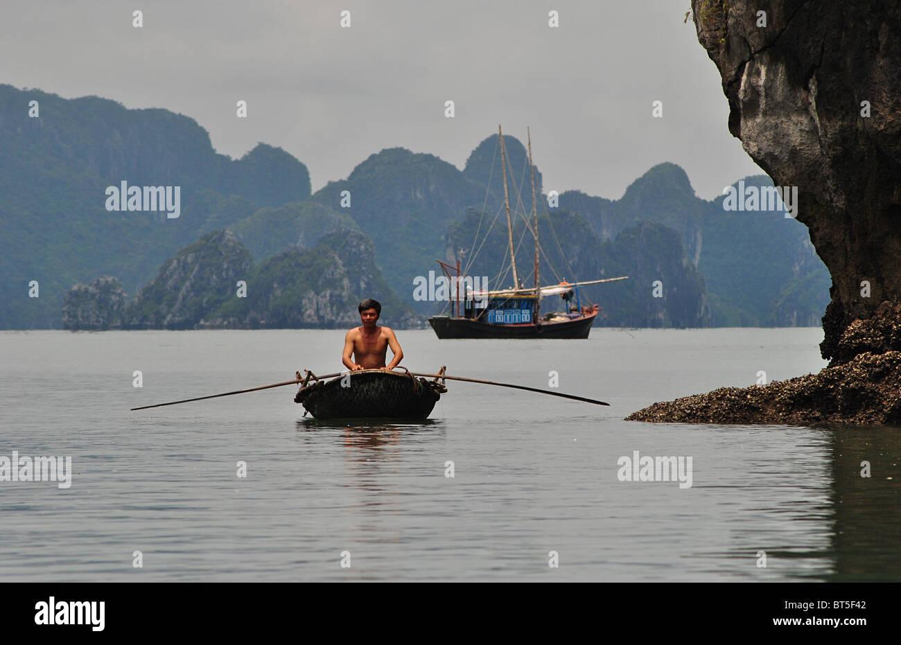 Trödel und Ruderboot in Halong Bucht, Vietnam Stockfoto