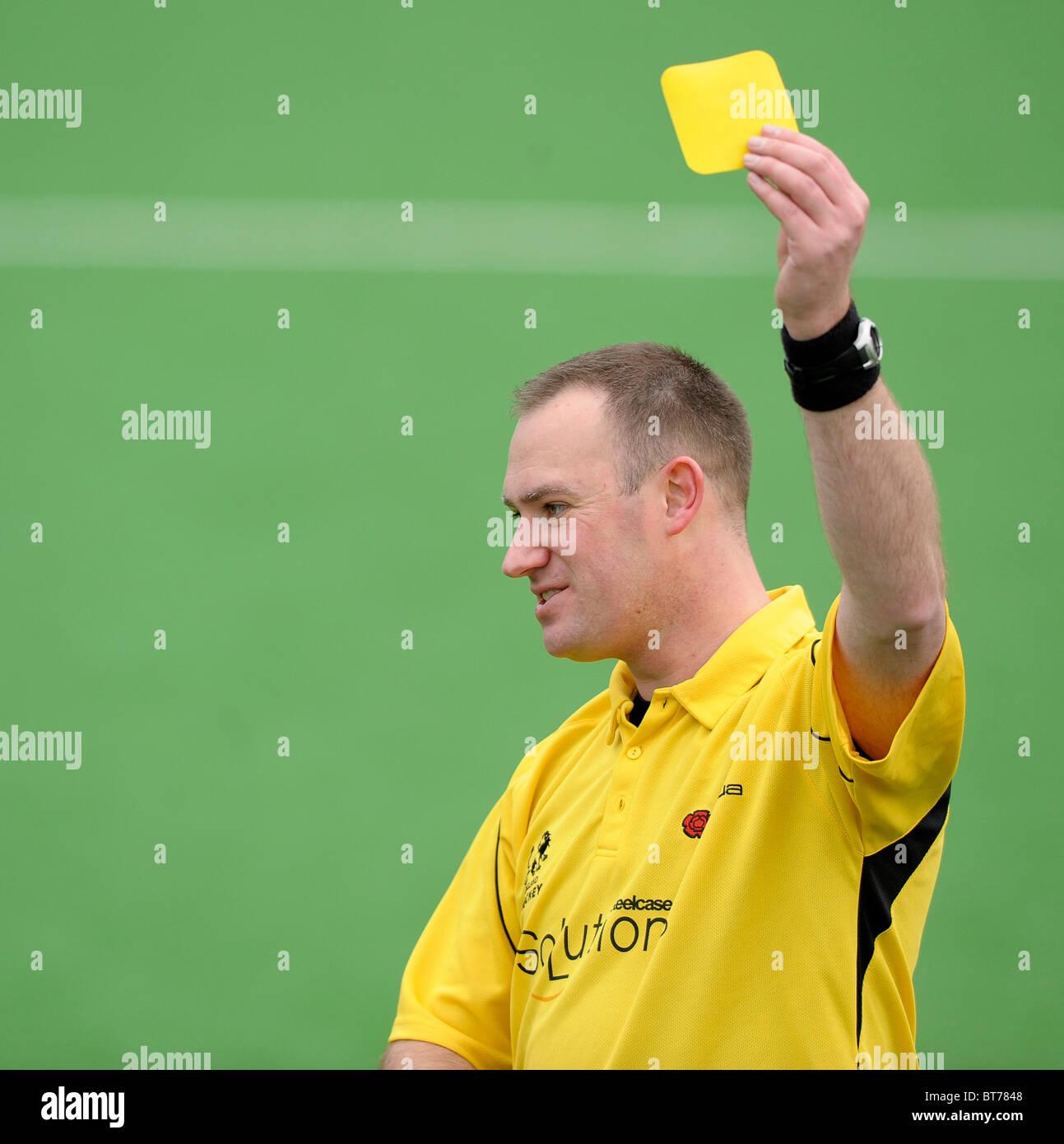 Obmann Richard Shaw zeigt eine gelbe Karte während ihres Spiels England Hockey League Premier Division in Surbiton Stockbild