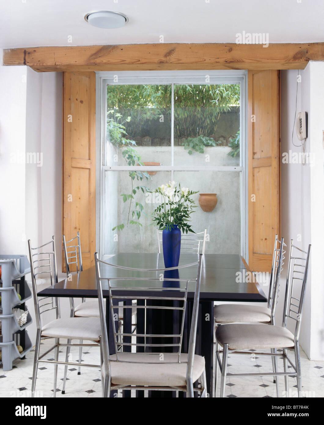 Metall  Und Weiße Stühle Am Schwarzen Tisch Im Modernen Keller Esszimmer  Mit Hölzernen Fensterläden Am Fenster