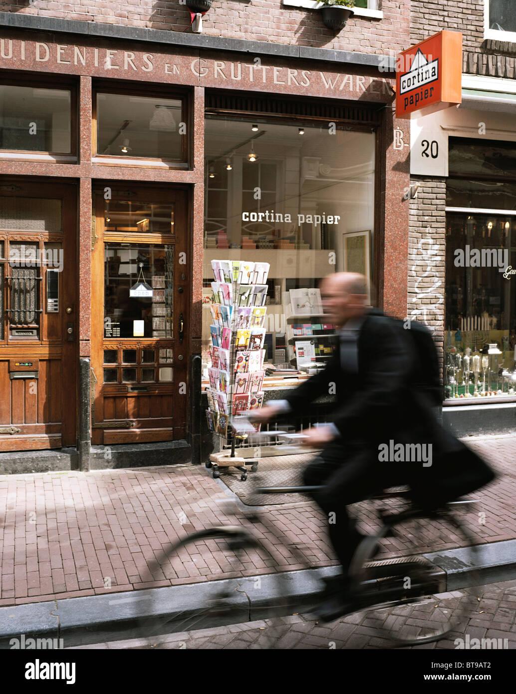 De Negen Straatjes in Amsterdam, wo ein Radfahrer Cortina Papier geht Stockbild