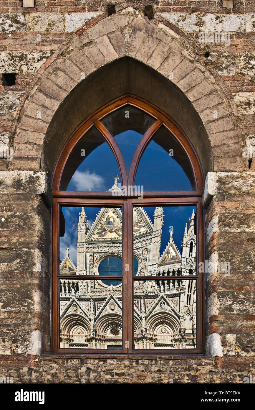 Duomo (Kathedrale) von Siena widerspiegelt im gotischen Fenster ...
