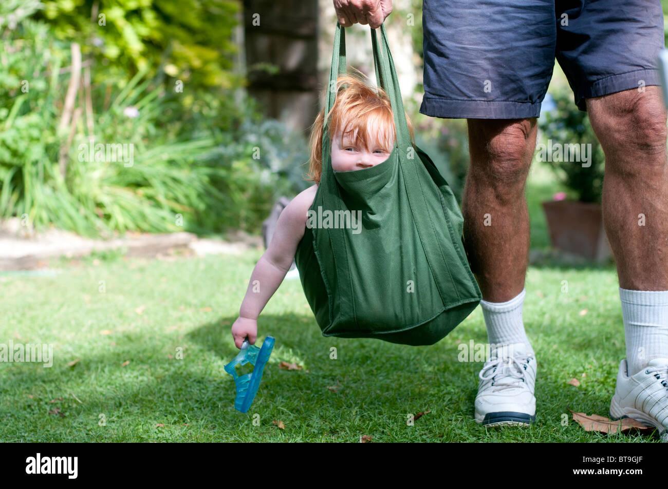 Ein senior Mann trägt ein kleines Kind in einer Tasche Stockfoto