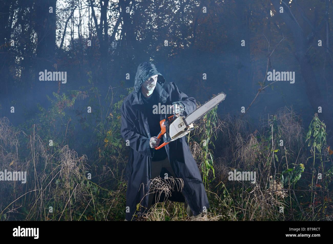 Unheimlich beängstigend Mann im schwarzen Mantel mit einer Kettensäge in einem nebligen Wald im Herbst Stockbild