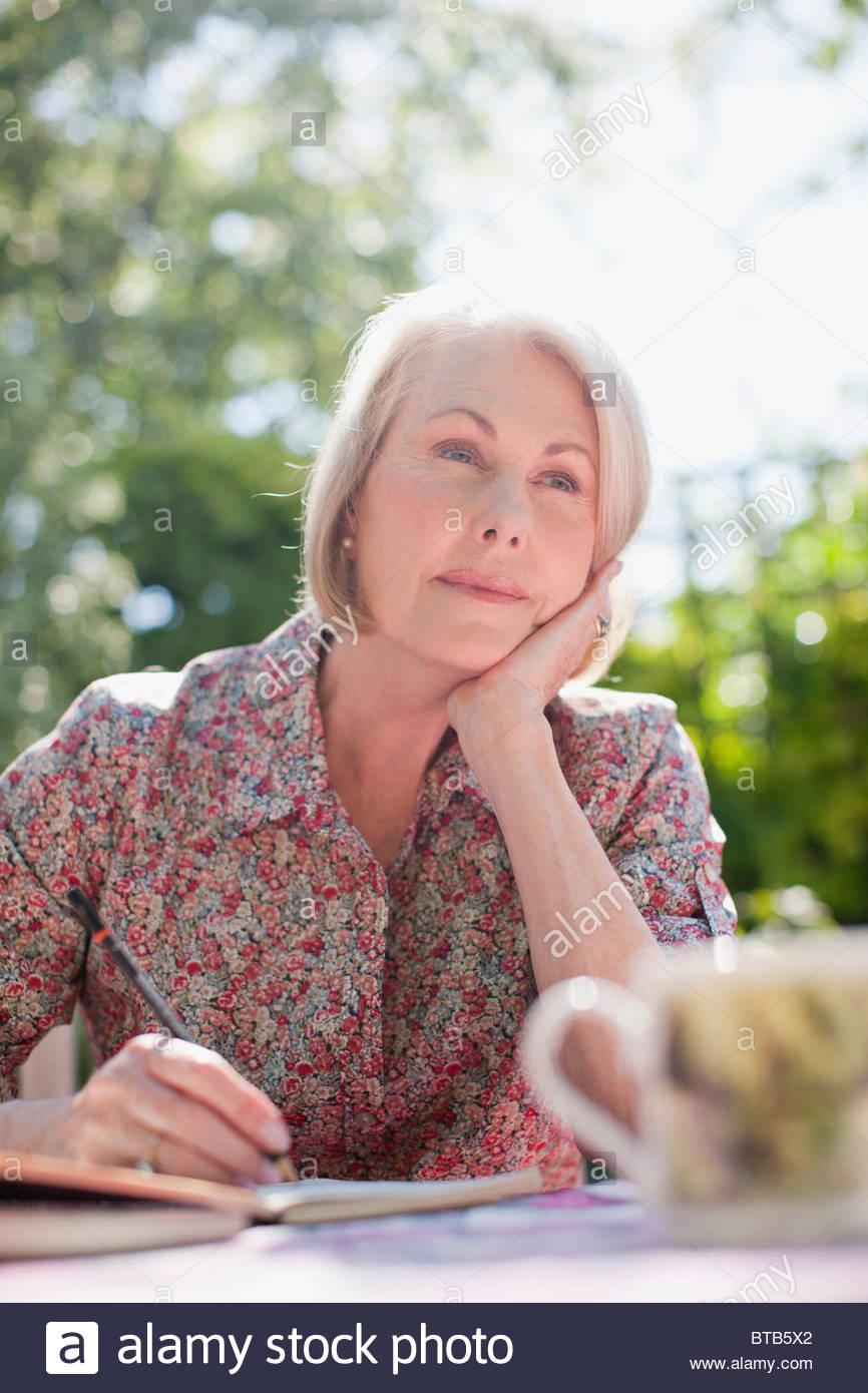 Nachdenkliche Frau in Fachzeitschrift an Terrassentisch Stockbild