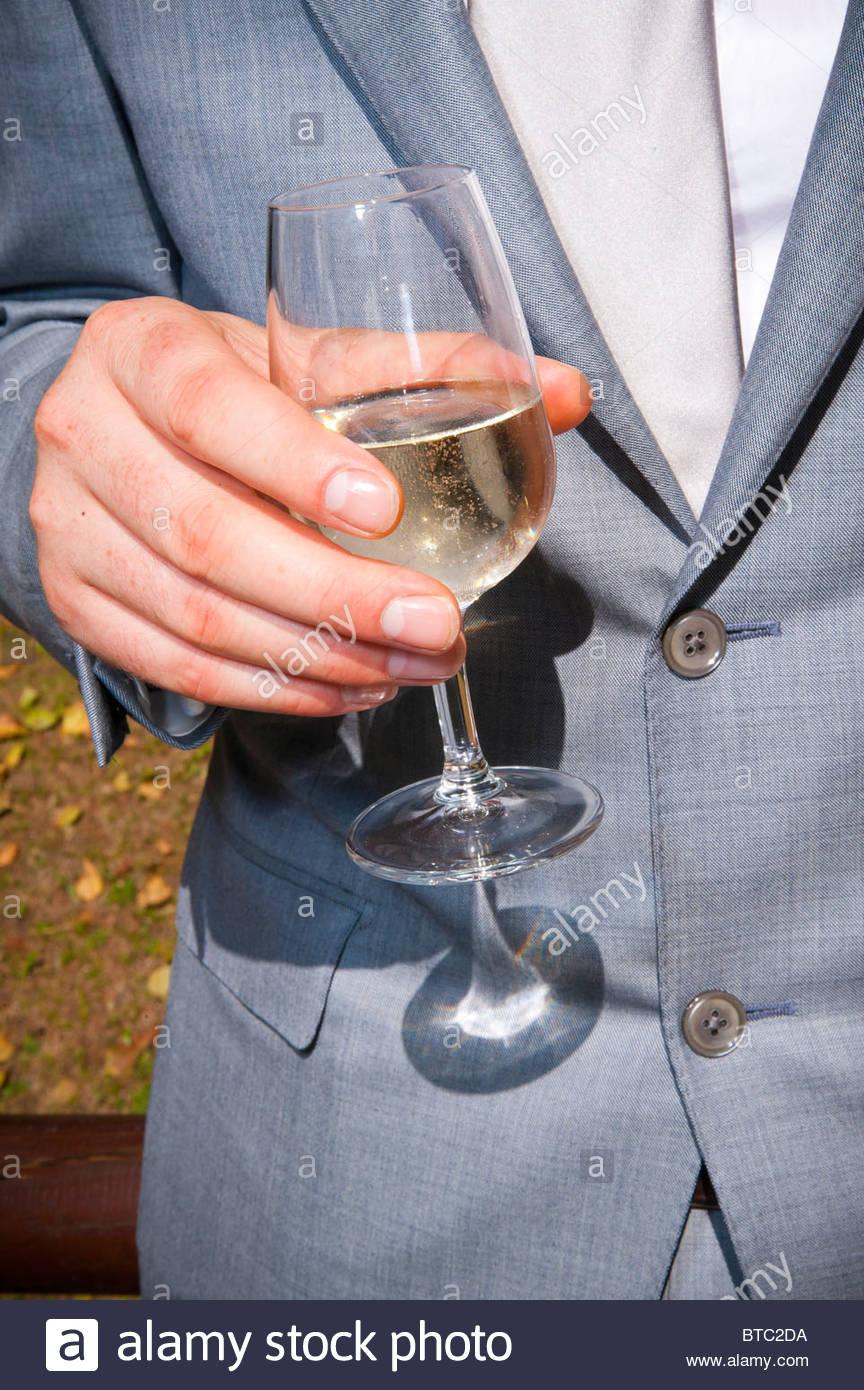 Mann hält ein Glas Weißwein Stockbild