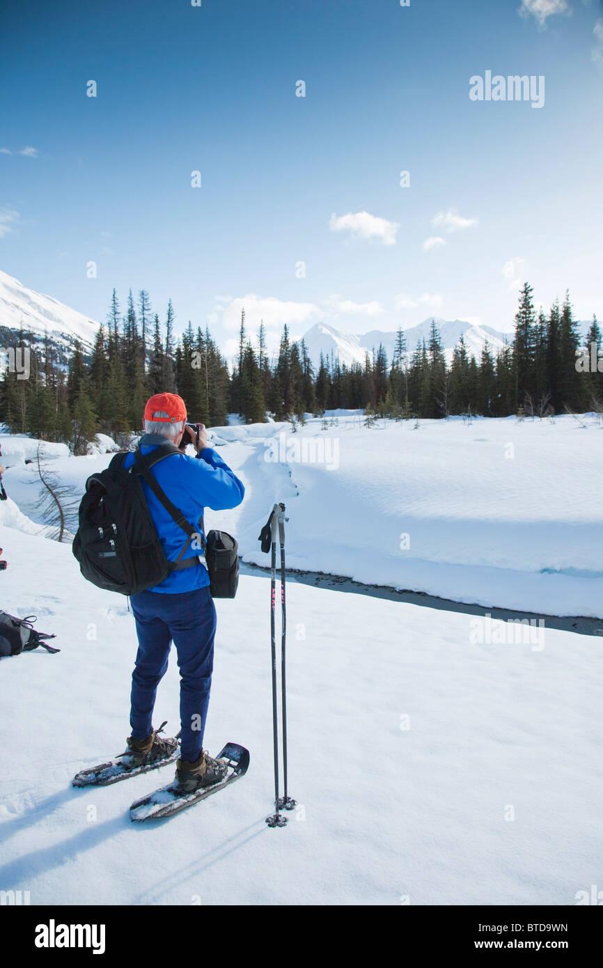 Mann auf Schneeschuhen sieht die Landschaft am Glacier Creek in der Nähe von Johnson Pass Trail, Chugach National Stockbild