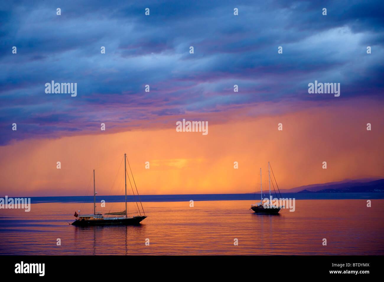 Segelboote bei Sonnenuntergang aus Mykonos, Kykladen Isalnd, Griechenland Stockfoto
