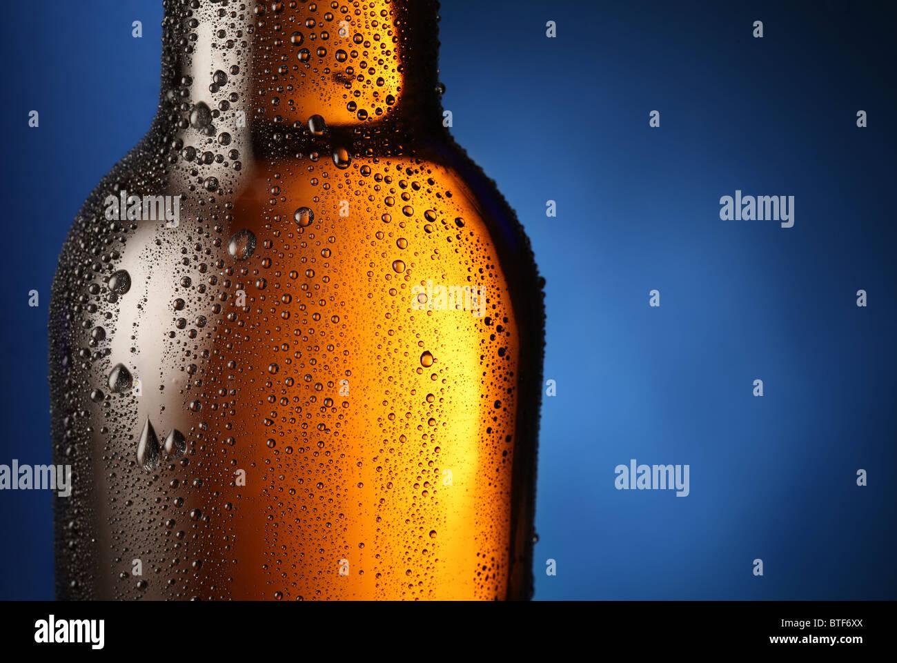 Eine Flasche Bier mit Tropfen auf einem blauen Hintergrund. Hautnah Teil der Flasche. Stockbild