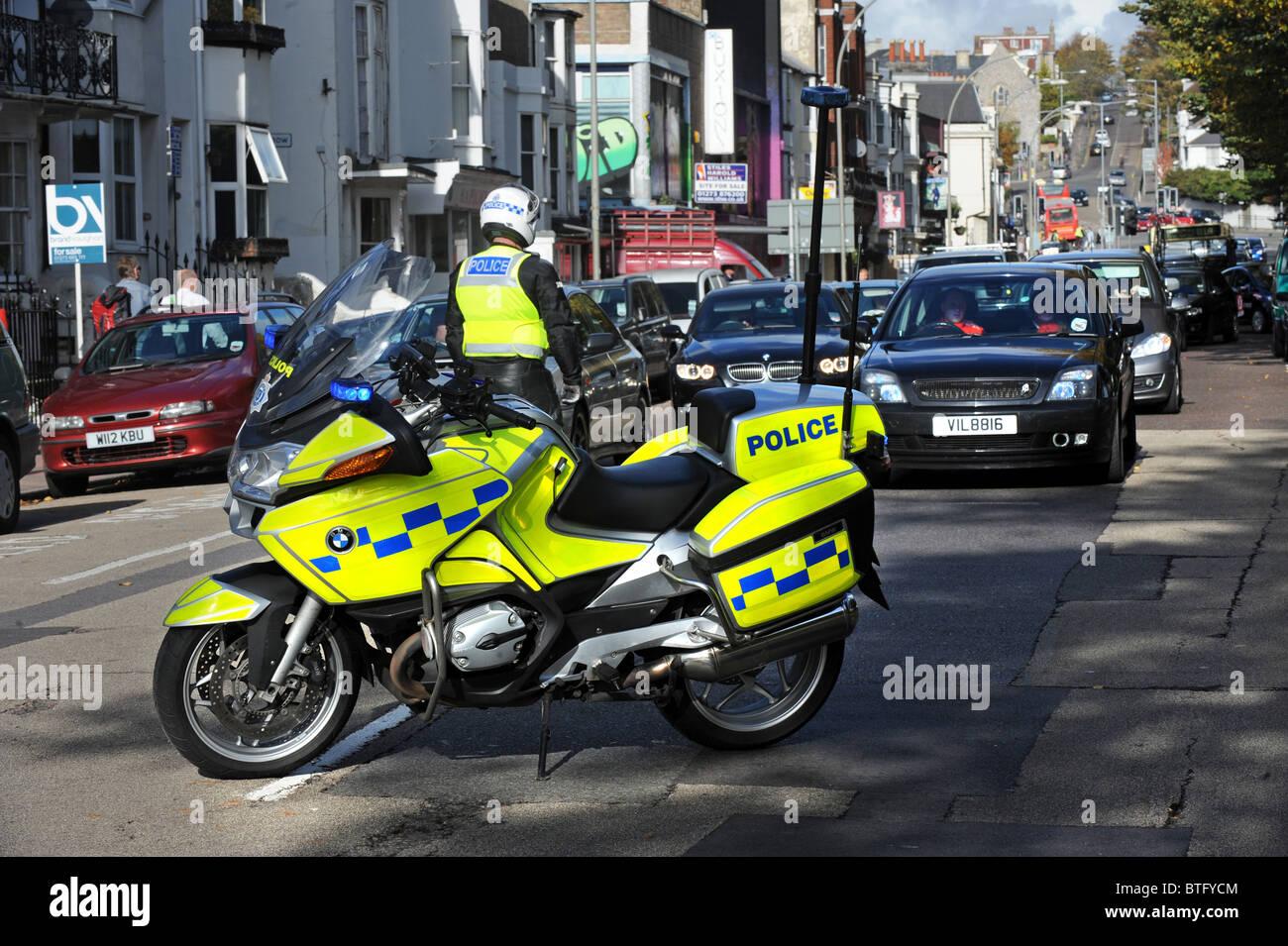 Ein Polizei-Motorradfahrer stoppt Verkehr, bevor ein Marsch über Kürzungen durch das Zentrum von Brighton Stockbild
