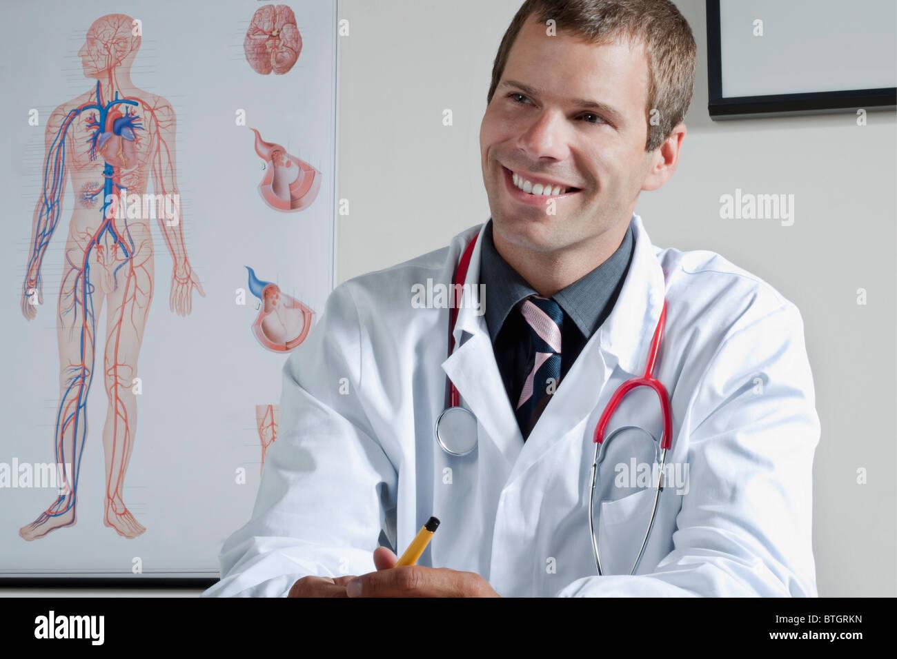 Arzt in seinem Büro mit Herz-Kreislauf-System Diagramm an Wand ...