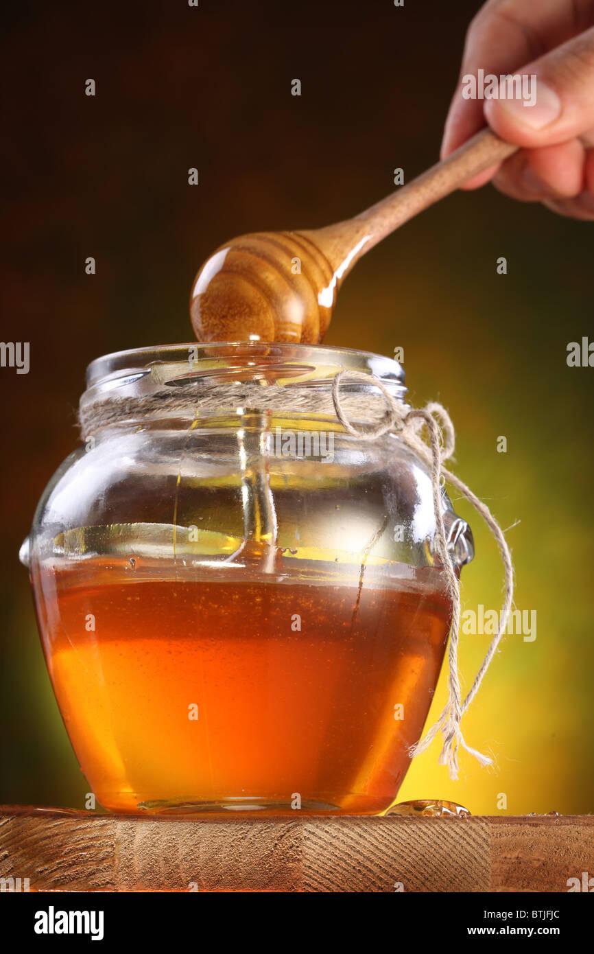 Hand hält Drizzler. Süßer Honig aus Drizzler in den Topf gießen. Stockbild