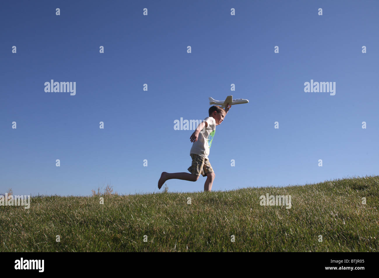 kleiner Junge läuft w/Spielzeugflugzeug, bereit, ihn fliegen zu lassen Stockbild