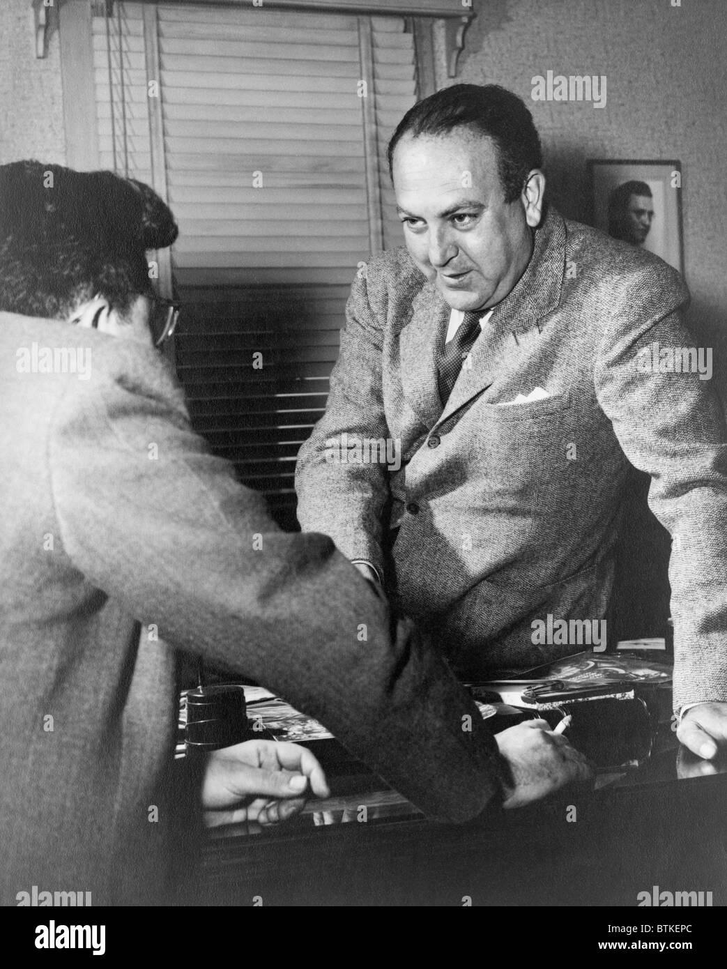 Regisseur Robert Wise (1914-2005) und Produzent Val Lewton (links) im Gespräch über einen Schreibtisch. Stockbild