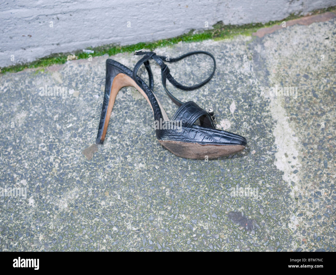 verlorene Womans high Heel Schuh auf Asphalt. Stockbild