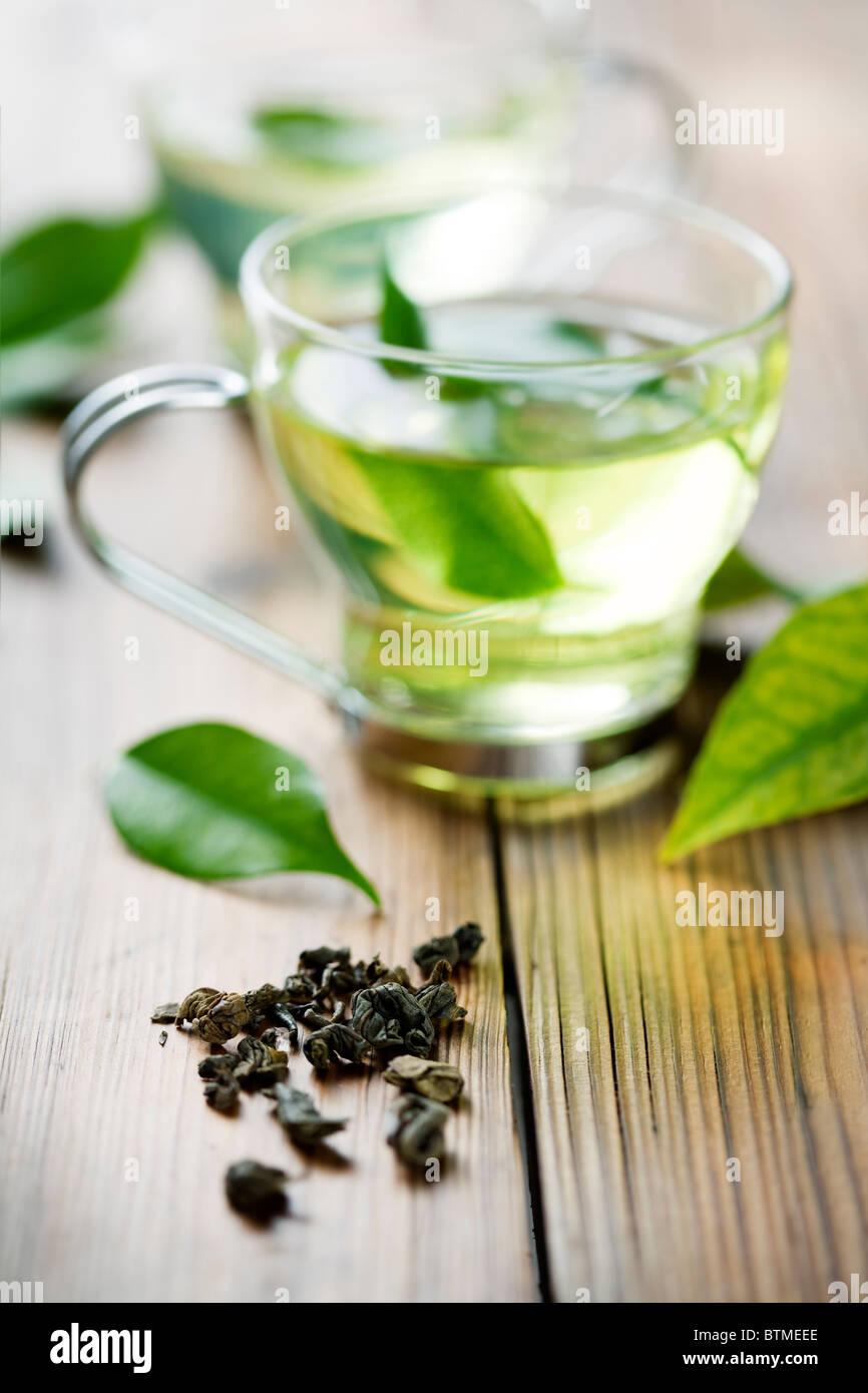 Nahaufnahme des trockenen grünem Tee und eine Tasse mit frischem grünem Tee. im Hintergrund, aus Fokus Stockbild