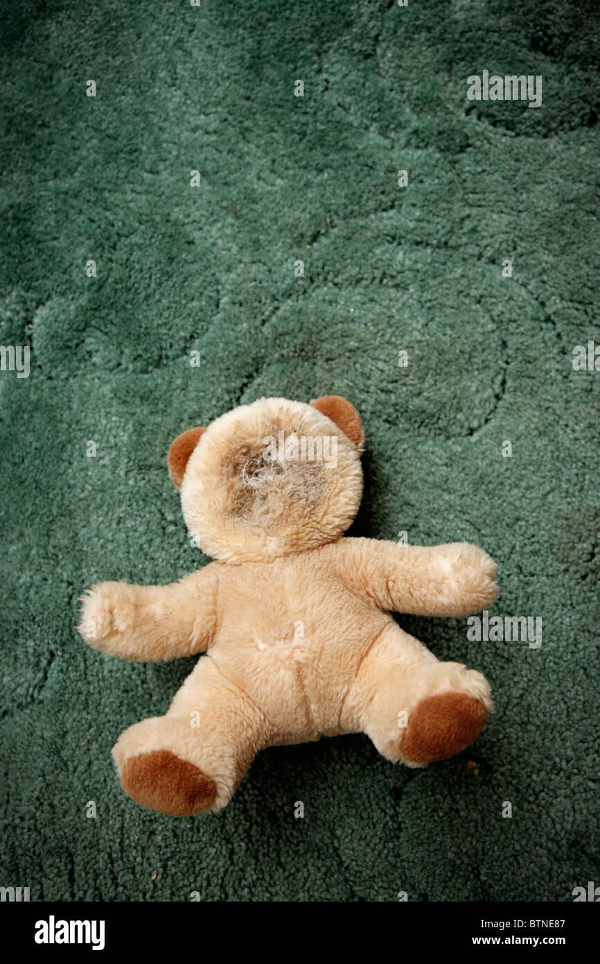 Sinister suchen Teddybär auf einem grünen Teppich mit kein Gesicht. Es war der Hund! Stockbild