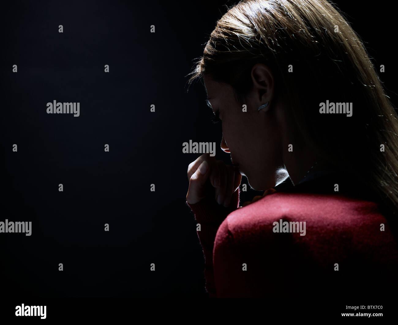 nachdenkliche Frau auf schwarzem Hintergrund, stellvertretend für das Konzept der Anonymität Stockfoto