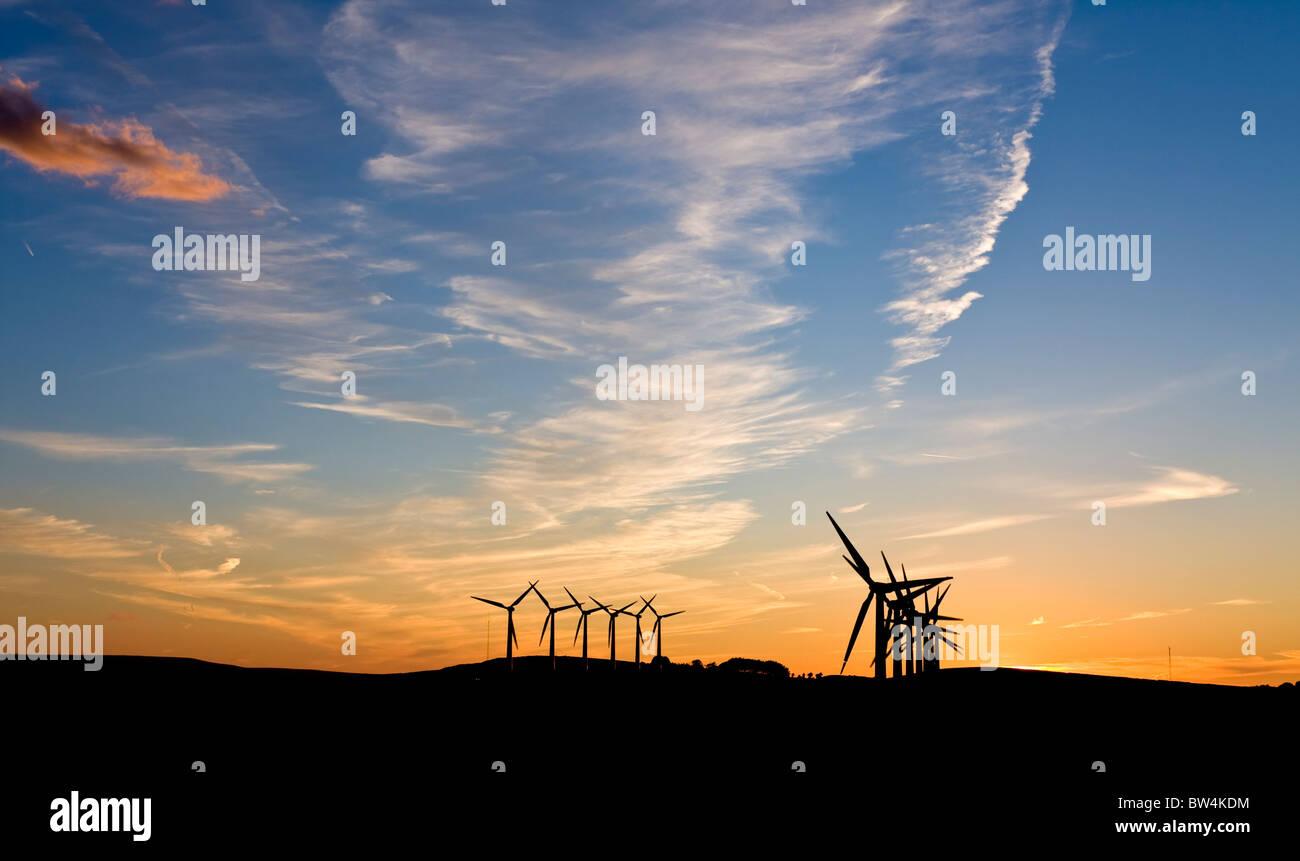 Windenergieanlagen gegen einen Sonnenuntergang Stockbild