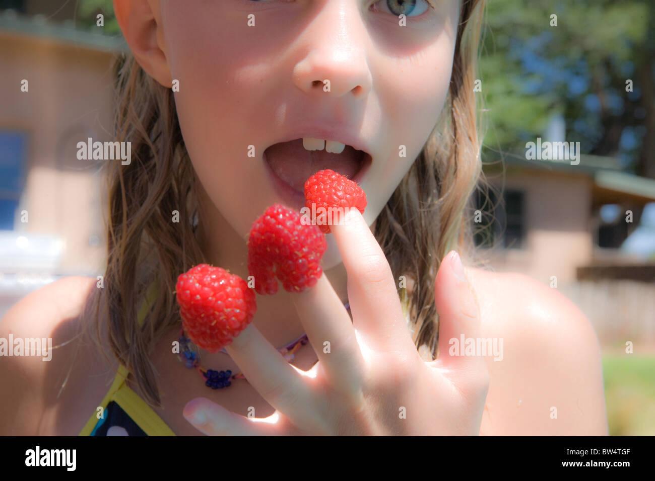 Mädchen mit Himbeeren auf ihren Fingerspitzen Mund offen Stockfoto