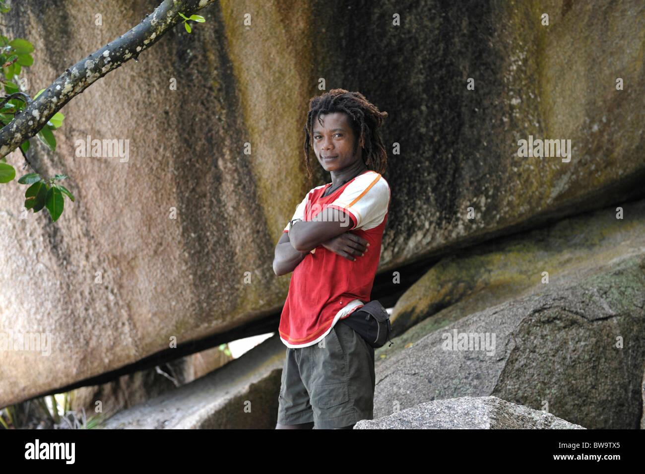 Jüngere dunkel-enthäuteten Mann am Grand Anse, La Digue, Seychellen Stockbild