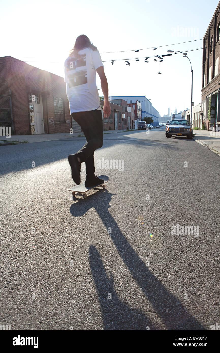 Skateboarder in städtischen Straße im Sonnenlicht Stockbild