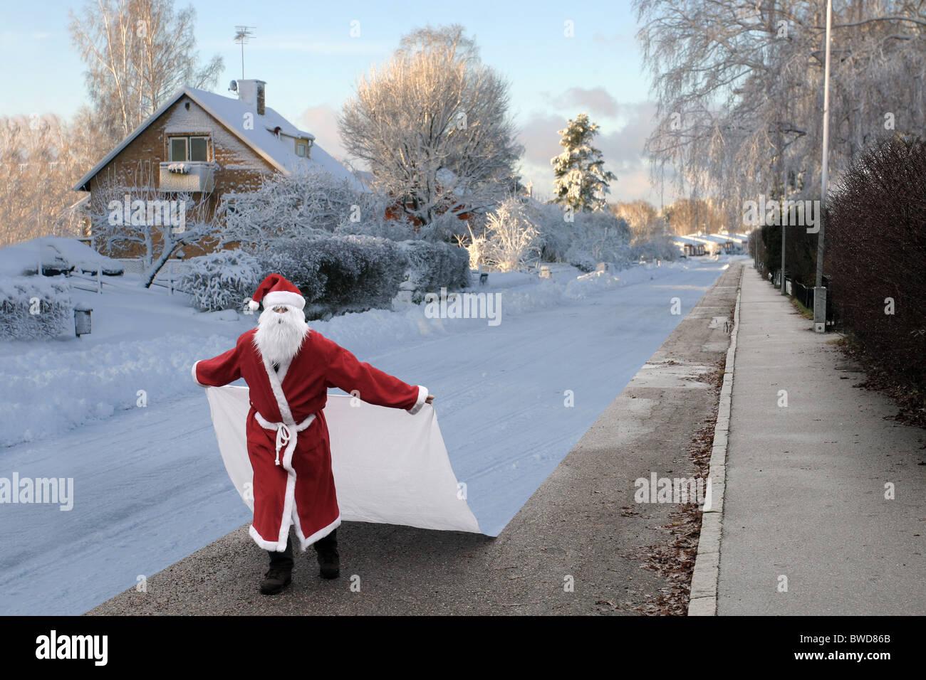 Santa Claus ändern der Saisons Winter durch ein Blatt von Schnee auf dem Boden zu legen. Stockbild