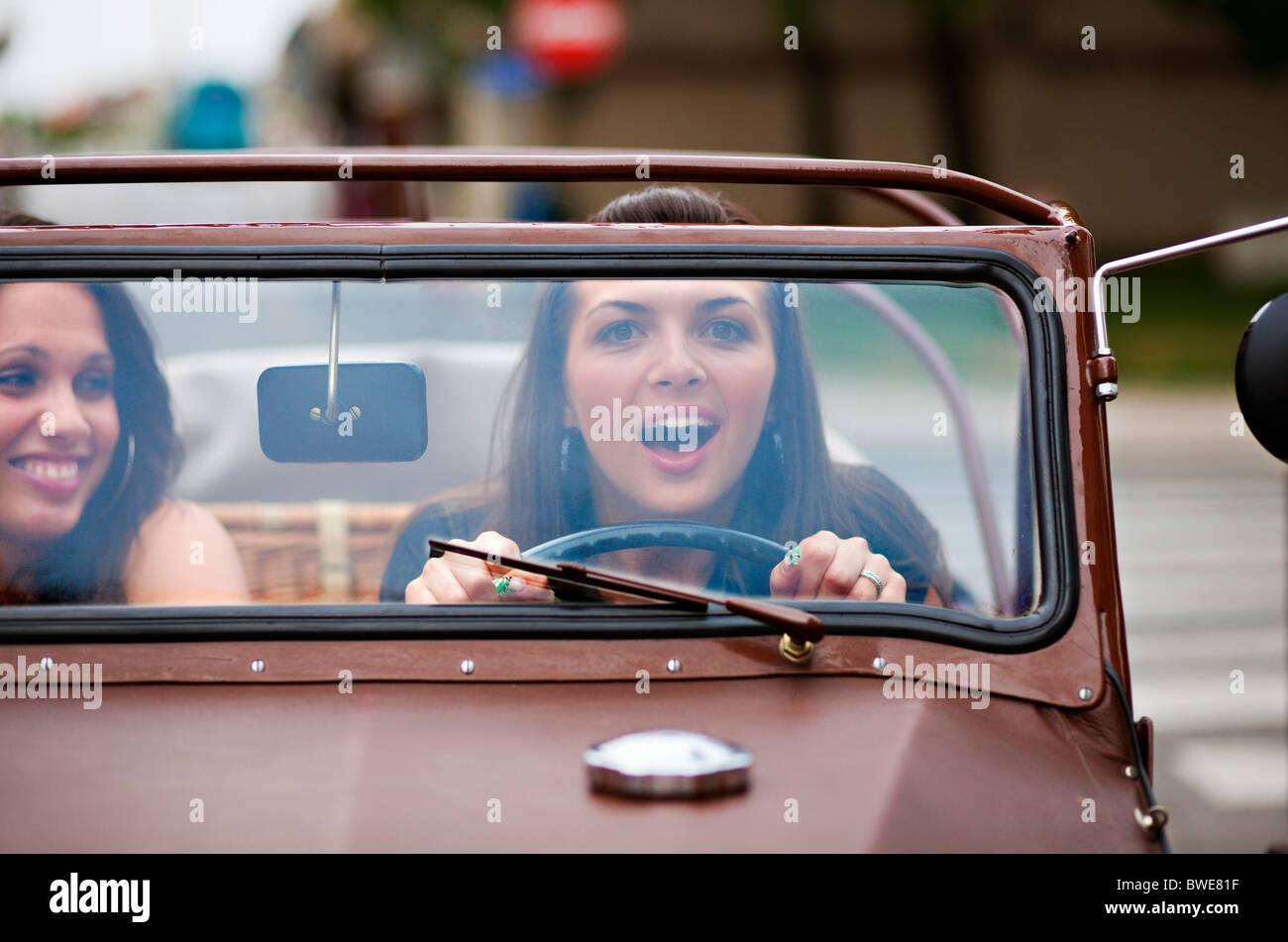 Junge Frauen fahren oldtimer Stockbild