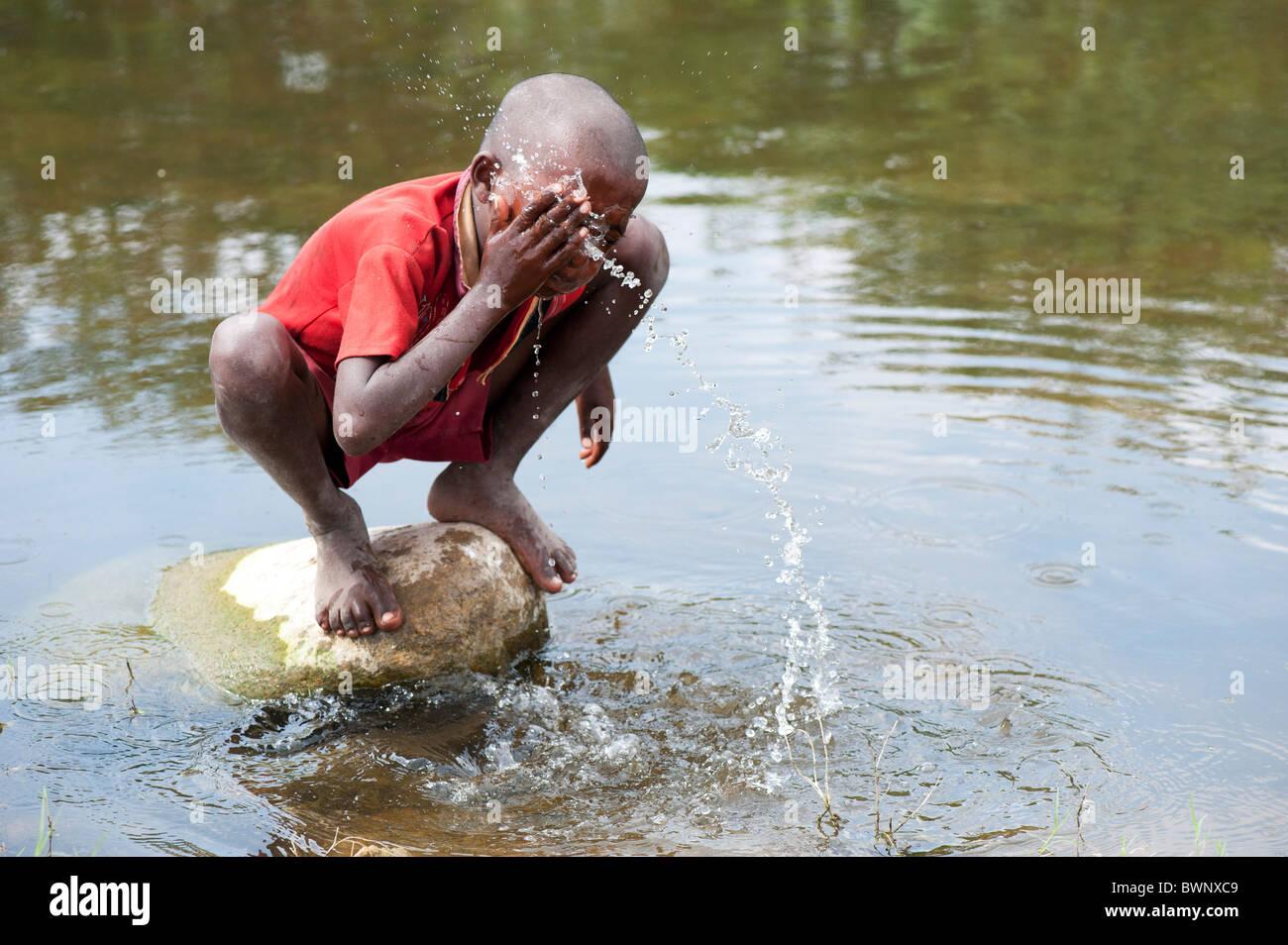 Indische street Boy waschen sich und Trinkwasser in einem Fluss in der indischen Landschaft. Andhra Pradesh, Indien Stockbild