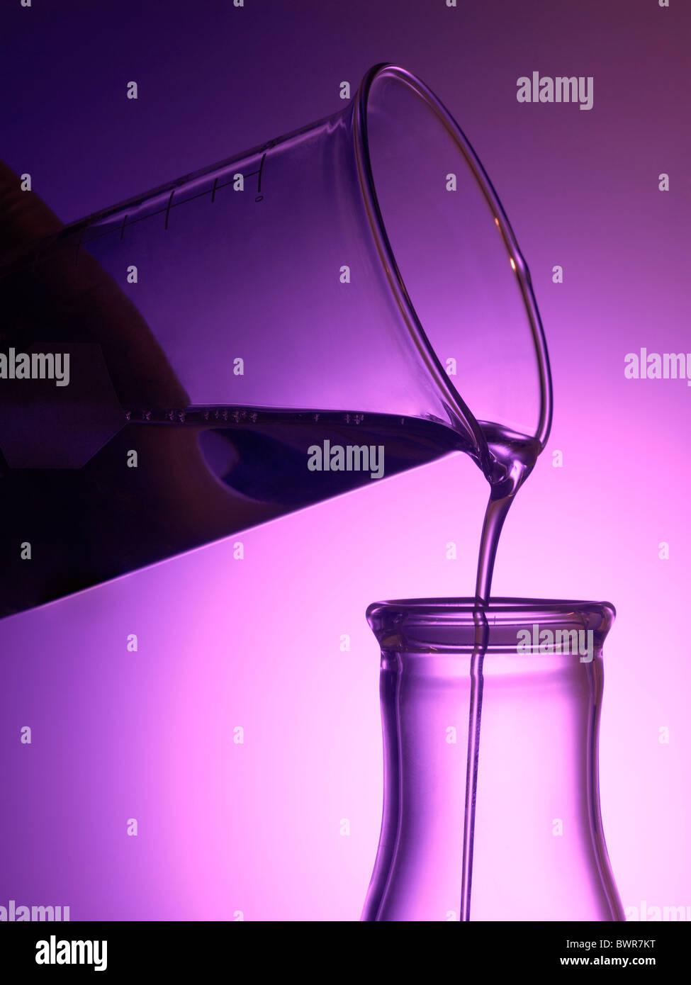Becherglas im Labor gießt flüssige Chemikalien in Becher Stockbild