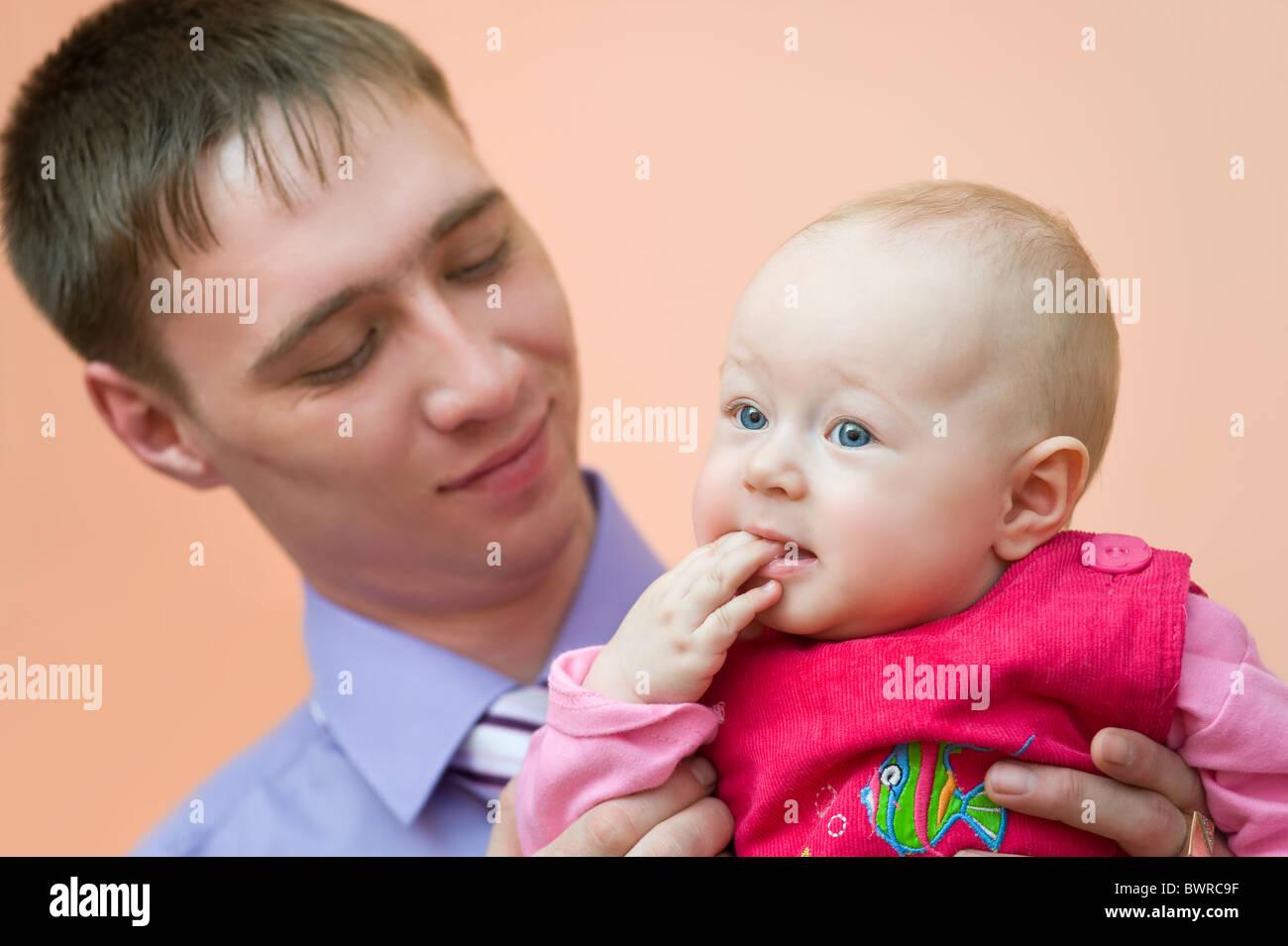 Europäische junger Mann schaut liebevoll seine kleine Tochter, die ihre Finger in den Mund nahm Stockfoto