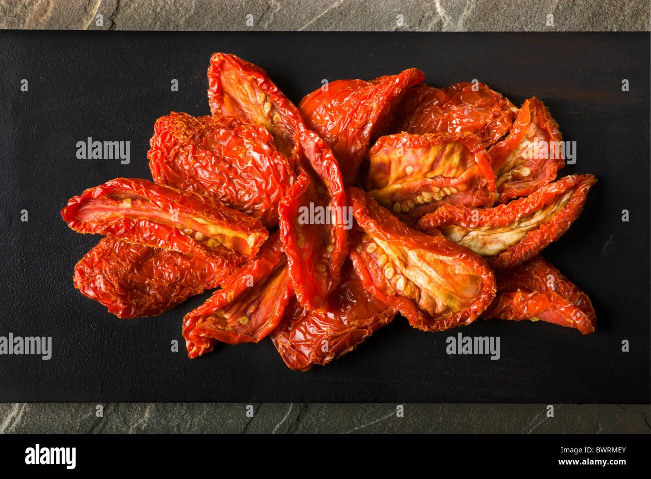 Ein paar Sun-Dried Tomaten auf einem schwarzen Hintergrund. Stockbild