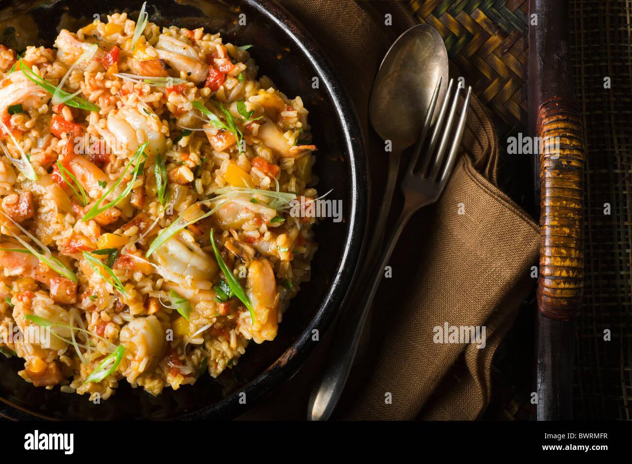 Brauner Reis mit Paprika, Tomaten, Schinken und Garnelen. Stockbild