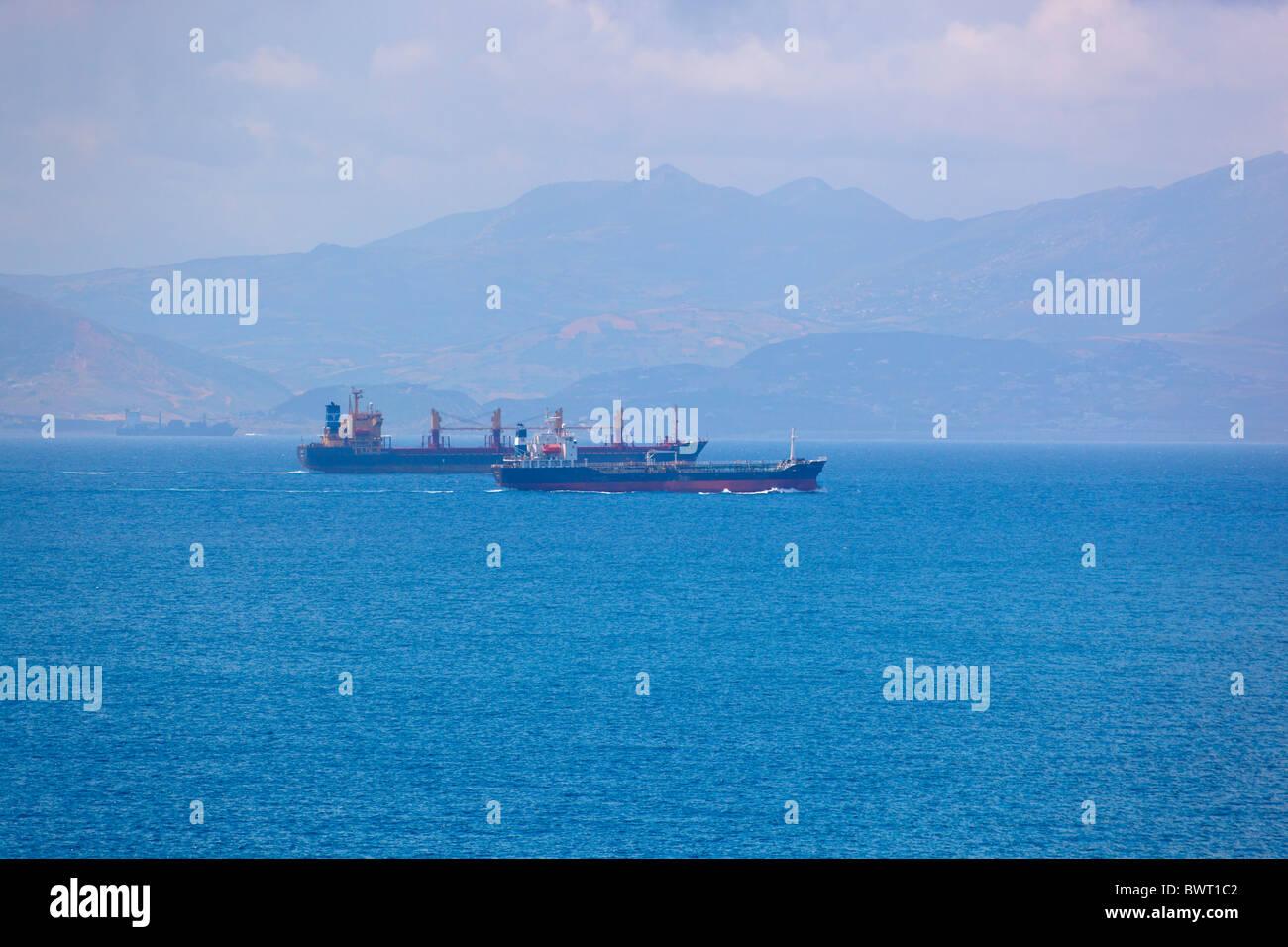 Frachtschiffe vorbei durch die Meerenge von Gibraltar zwischen Spanien und Marokko. Marokko ist im Hintergrund zu Stockbild