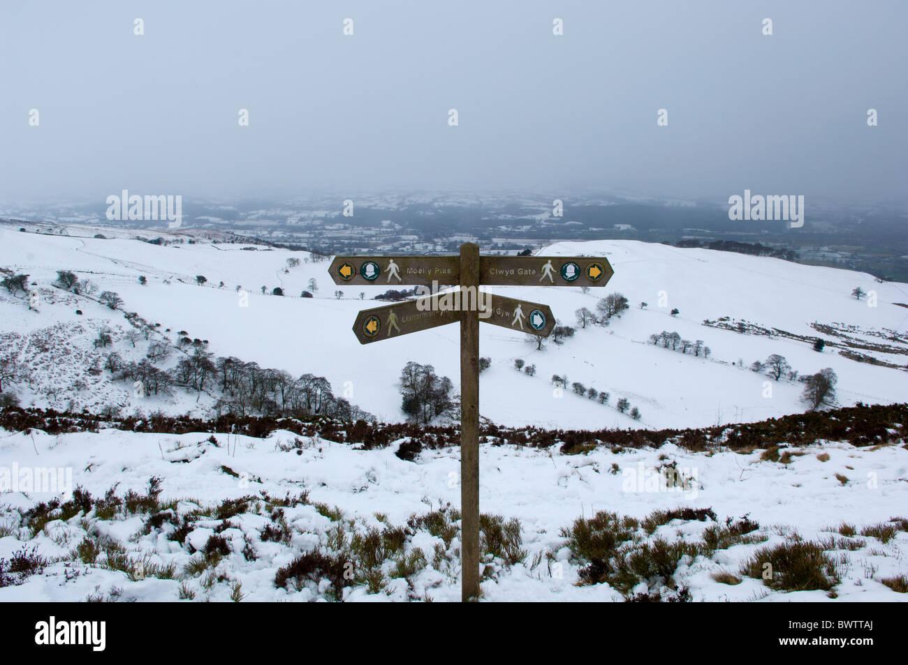 Eine schneereiche Winter-Szene zeigt einen Finger Post auf Offas Dyke Wanderweg Nr. Moel Gwm. Vale von Clwyd sichtbar Stockbild