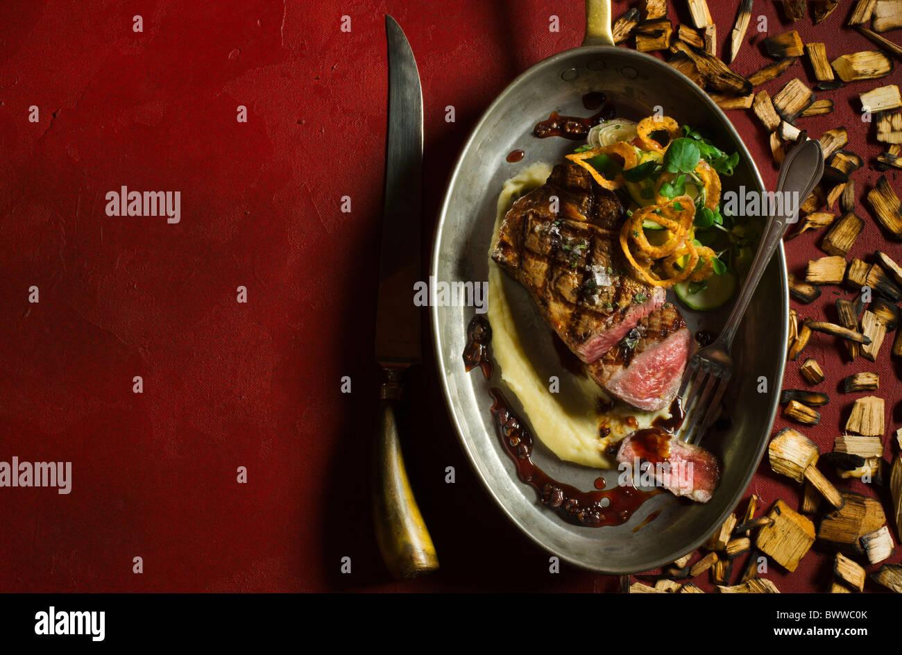 Ribeye Rind, pochiert in Fat Duck und frisch vom Grill mit Mesquite-Holz-Chips, serviert mit Kartoffelpüree, Stockbild