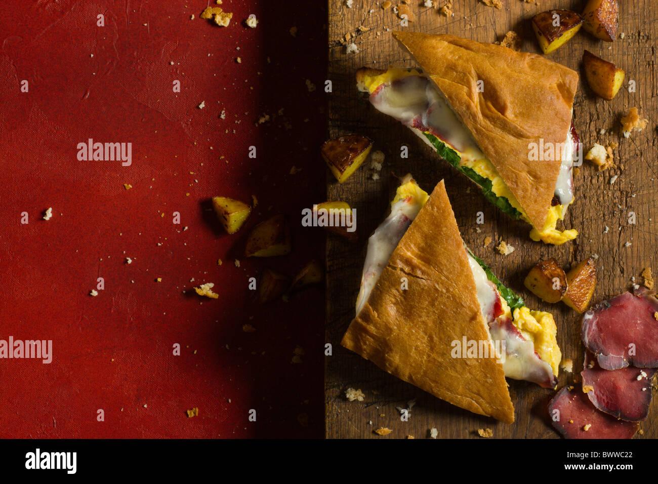 Ein heißes Panino mit Focaccia, Wild Speck, Arugola, Rührei und Käse, eine rustikale Holz Schneidebrett Stockbild