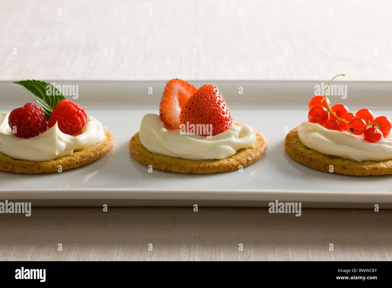 Kekse mit cremiger Käse verteilen, garniert mit Himbeeren, Minze, Erdbeeren, rote Johannisbeere und gelben Stockbild