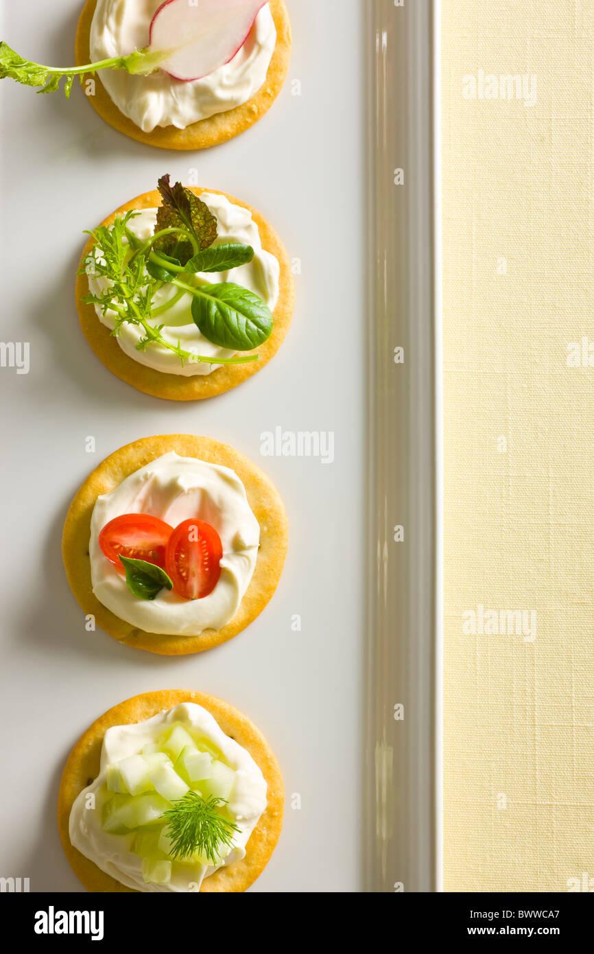 Kekse mit cremiger Käse verbreiten, garniert mit Tomaten, Basilikum, Gurken, Dill, gemischte grün und Stockbild