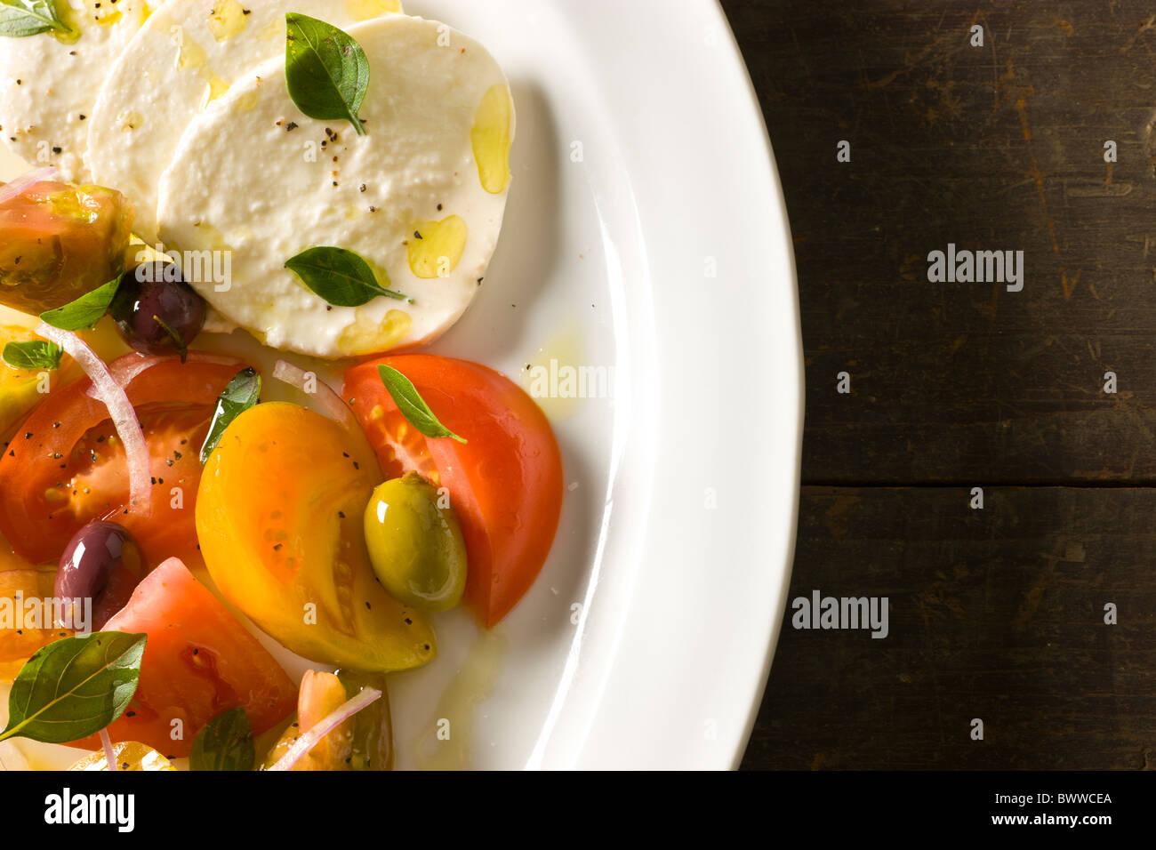 Mozzarella mit Tomaten und Oliven, Olivenöl und frischer Oregano Stockbild